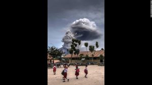 School children play while the ominous and threatening Mount Sinabung volcano looks poised to erupt.
