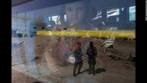 Soldiers are seen in the reflection from a bus window carrying children and other civilians out of a suburb of Damascus, Syria. The warring forces in the six year old civil war that has murdered thousands, agreed to allow people to escape the suburb so that the murder could resume between the warring factions' soldiers.