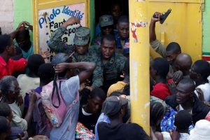 People in haiti rush soldiers at a food depot as the island continues to recover from the devastation of Hurricane Matthew.